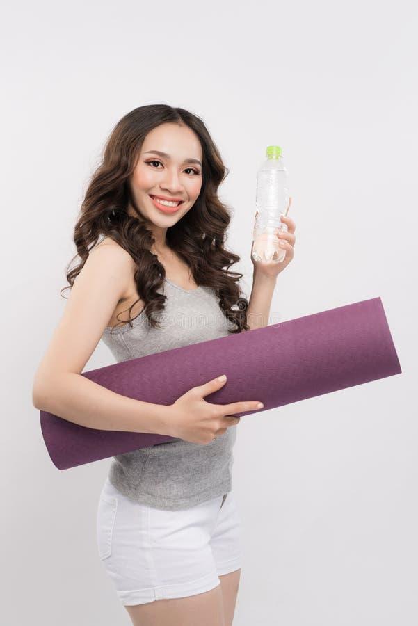 Giovane donna asiatica allegra che tiene una bottiglia con acqua e yoga fotografie stock libere da diritti