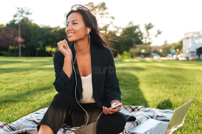 Giovane donna asiatica allegra di affari che ascolta la musica, mentre con riferimento a fotografia stock