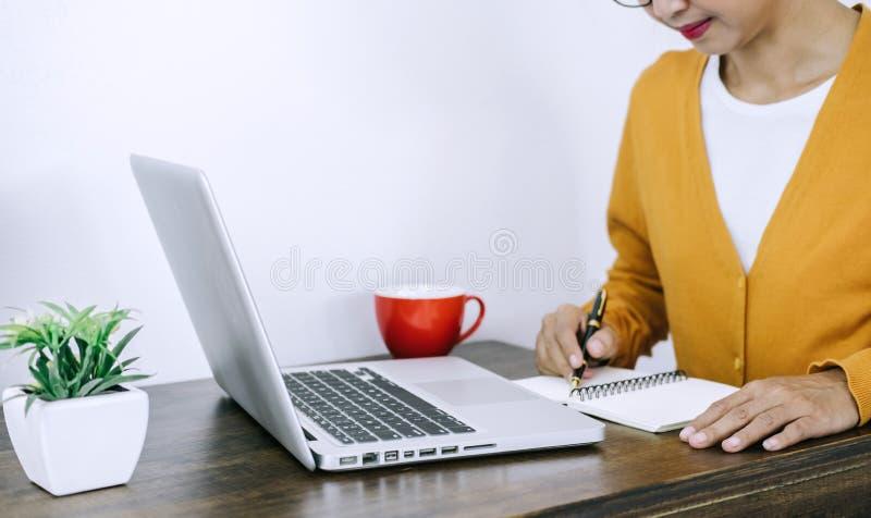 Giovane donna asiatica casuale felice che lavora nell'ufficio domestico o piccolo w immagini stock