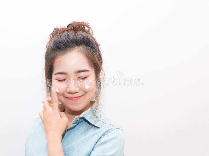 Giovane donna asiatica che applica crema d'idratazione sul suo fronte immagine stock