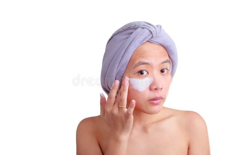 Giovane donna asiatica che applica crema sul suo fronte fotografia stock libera da diritti
