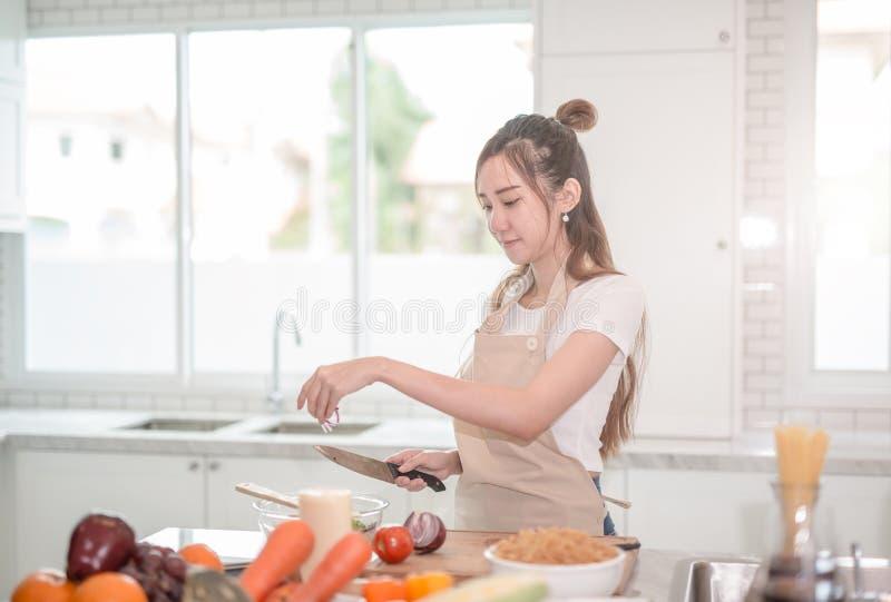 Giovane donna asiatica che cucina alimento sano nella cucina fotografia stock libera da diritti