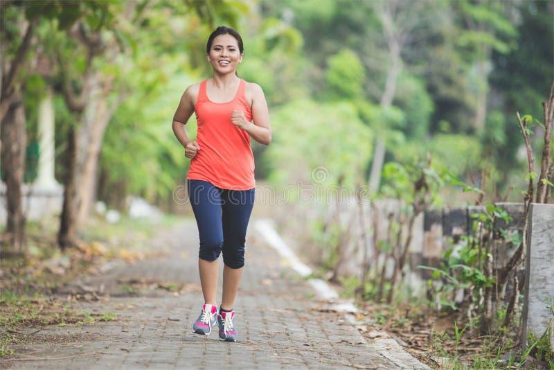 Giovane donna asiatica che fa esercizio all'aperto in un parco, pareggiante fotografie stock