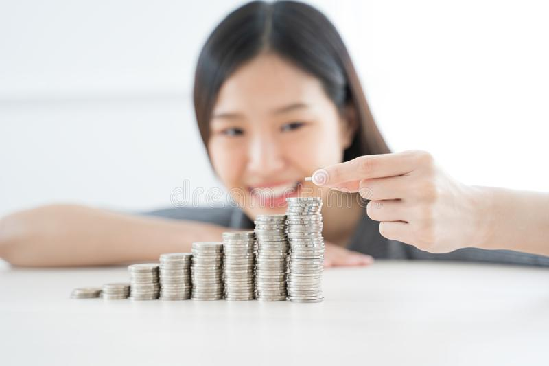 Giovane donna asiatica che fa pila delle monete investa il concetto di risparmio di finanza fotografia stock libera da diritti