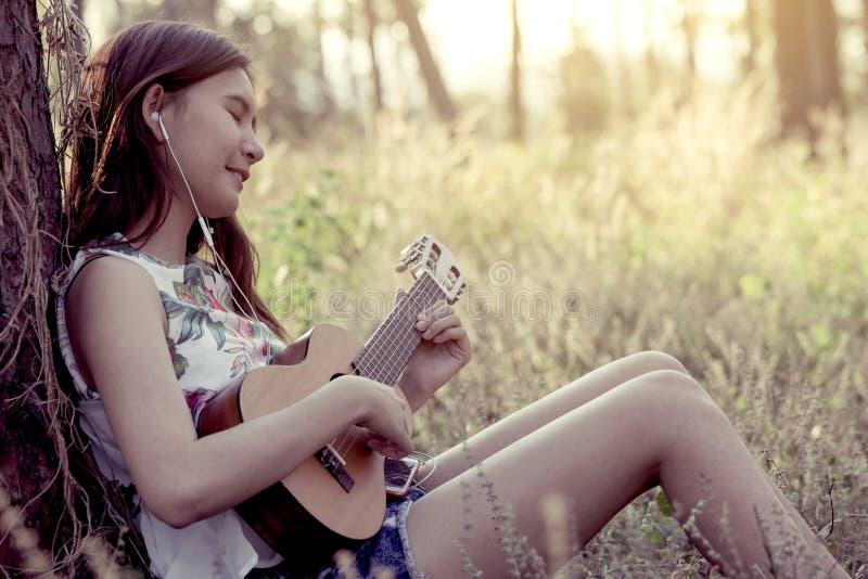 Giovane donna asiatica che gioca guitalele acustico immagini stock libere da diritti