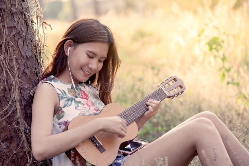 Giovane donna asiatica che gioca guitalele acustico fotografie stock