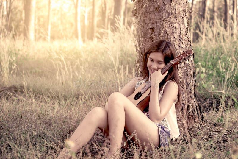 Giovane donna asiatica che gioca guitalele acustico immagini stock