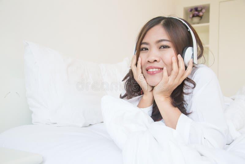 Giovane donna asiatica che gode della musica al letto fotografia stock