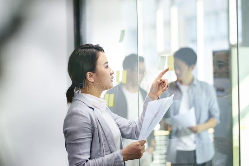 Giovane donna asiatica che lavora nella sala riunioni immagini stock libere da diritti