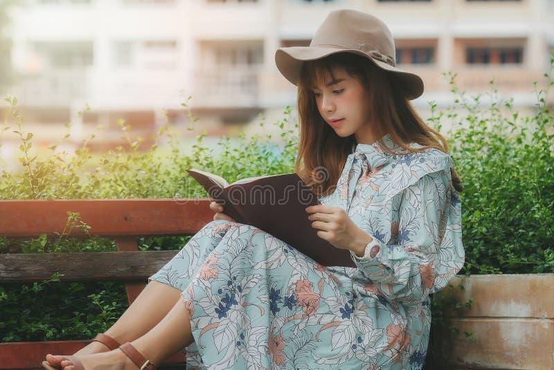 Giovane donna asiatica che legge un libro sul banco immagine stock