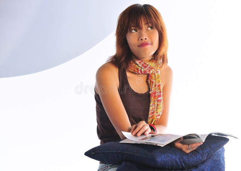 Giovane donna asiatica che legge uno scomparto fotografia stock libera da diritti