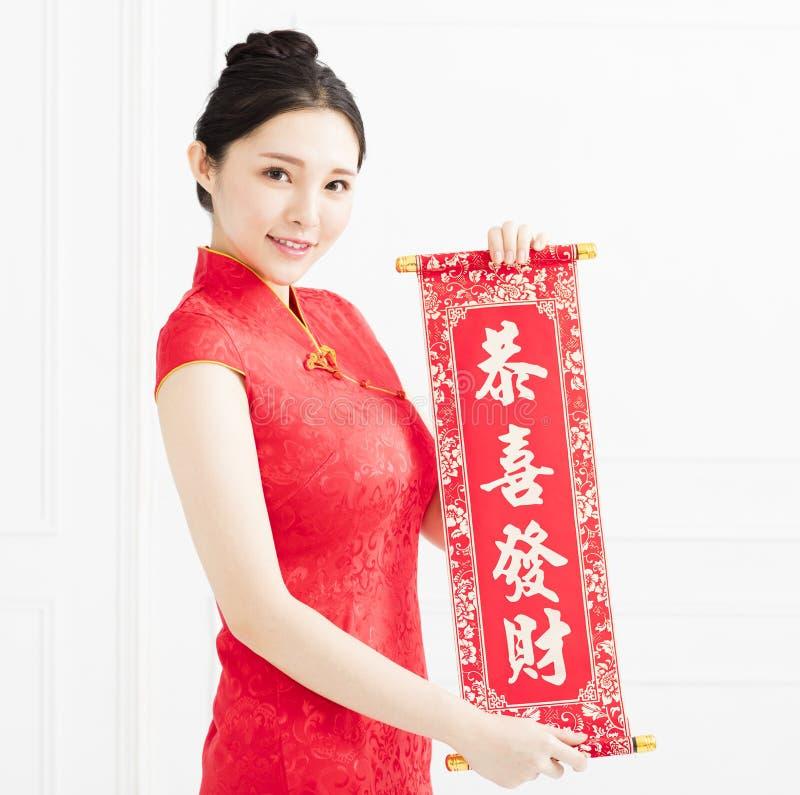 Giovane donna asiatica che mostra i distici rossi immagine stock libera da diritti