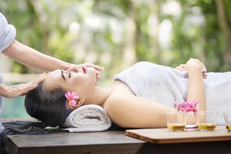 Giovane donna asiatica che ottiene trattamento del fronte della pelle immagini stock