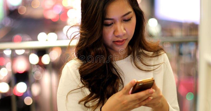 Giovane donna asiatica che per mezzo del suo telefono cellulare fotografia stock libera da diritti