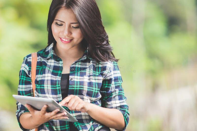 Giovane donna asiatica che per mezzo di un pc della compressa mentre camminando sul parco immagini stock
