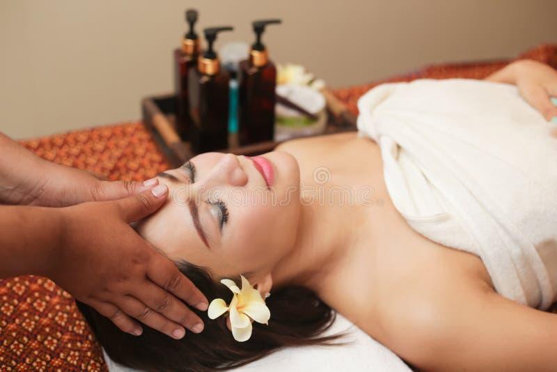 Giovane donna asiatica che riceve massaggio capo alla stazione termale di bellezza fotografia stock libera da diritti