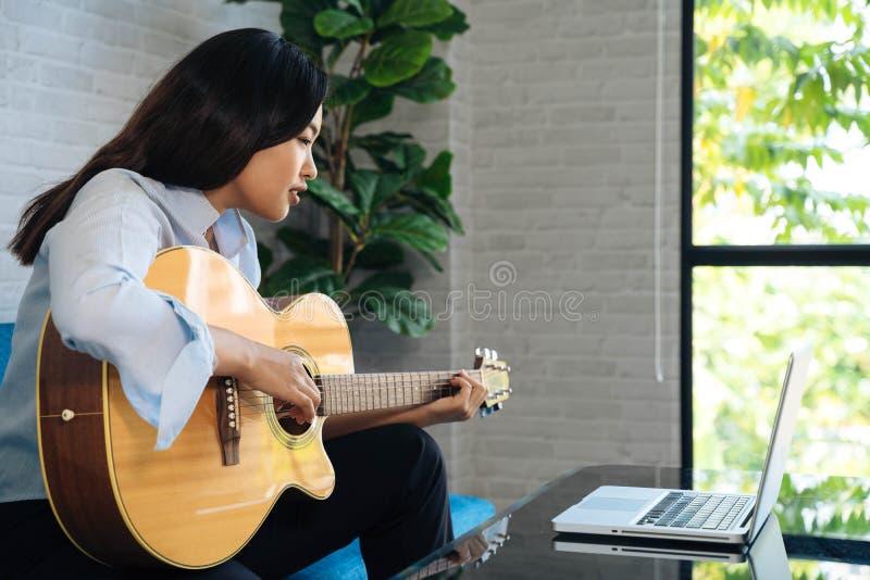 Giovane donna asiatica che si esercita e impara a suonare la chitarra su un computer portatile Chitarrista donna che guarda fotografia stock