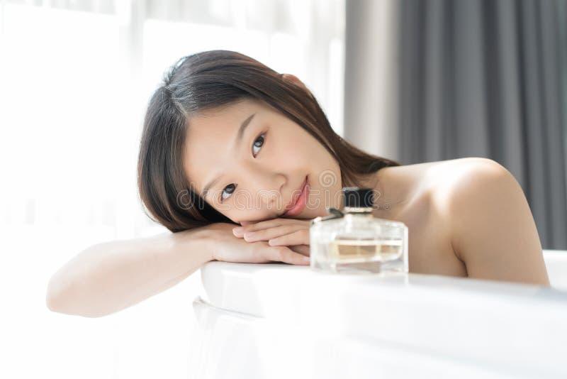 Giovane donna asiatica che si rilassa in un bagno Concetto femminile dello skincare fotografie stock
