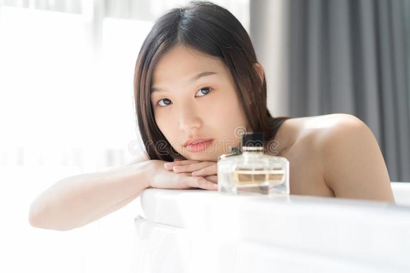 Giovane donna asiatica che si rilassa in un bagno Concetto femminile dello skincare fotografia stock libera da diritti