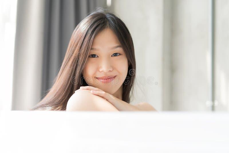 Giovane donna asiatica che si rilassa in un bagno Concetto femminile dello skincare fotografia stock