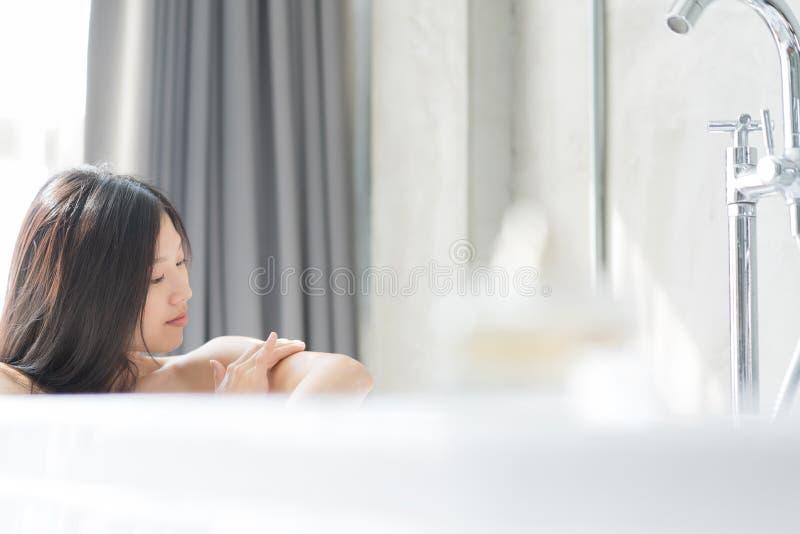 Giovane donna asiatica che si rilassa in un bagno Concetto femminile dello skincare immagini stock
