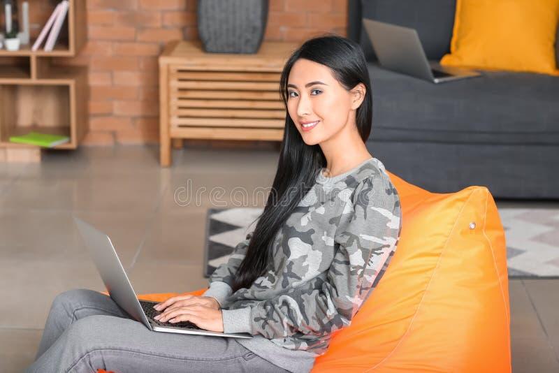 Giovane donna asiatica che studia con il computer portatile a casa immagine stock