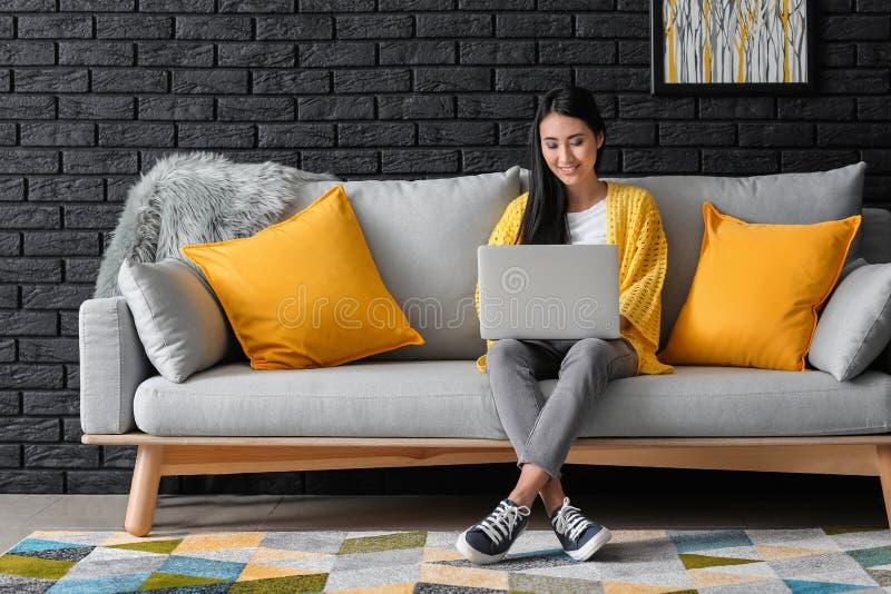 Giovane donna asiatica che studia con il computer portatile a casa immagini stock
