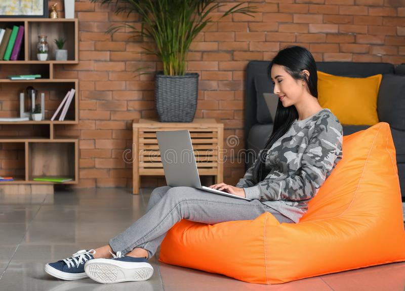 Giovane donna asiatica che studia con il computer portatile a casa fotografia stock libera da diritti