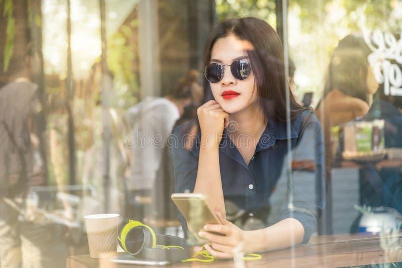 Giovane donna asiatica che tiene il suo smartphone in una caffetteria fotografia stock libera da diritti