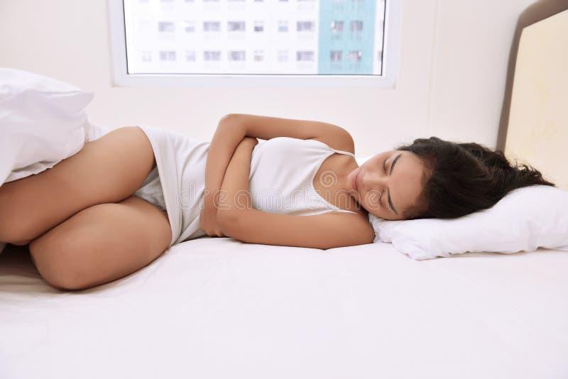 Giovane donna asiatica con comodità a letto immagine stock libera da diritti