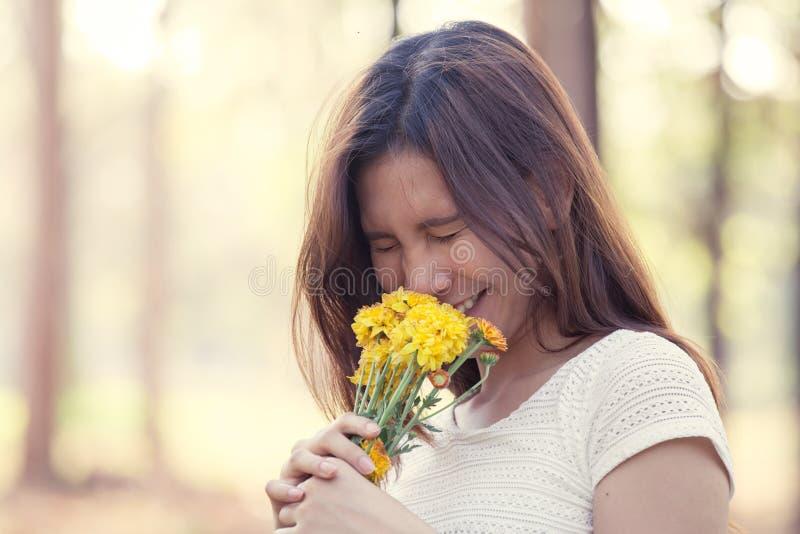 Giovane donna asiatica con il fiore nel parco immagine stock libera da diritti