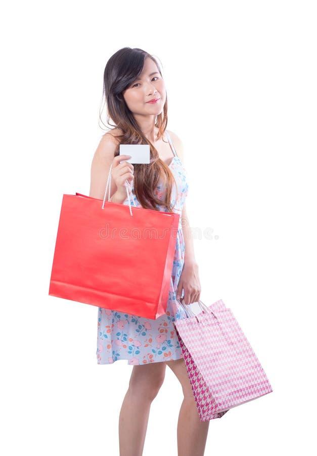 Giovane donna asiatica con il vestito rosso che tiene una carta della carta di credito e del sacco di carta isolata fotografia stock