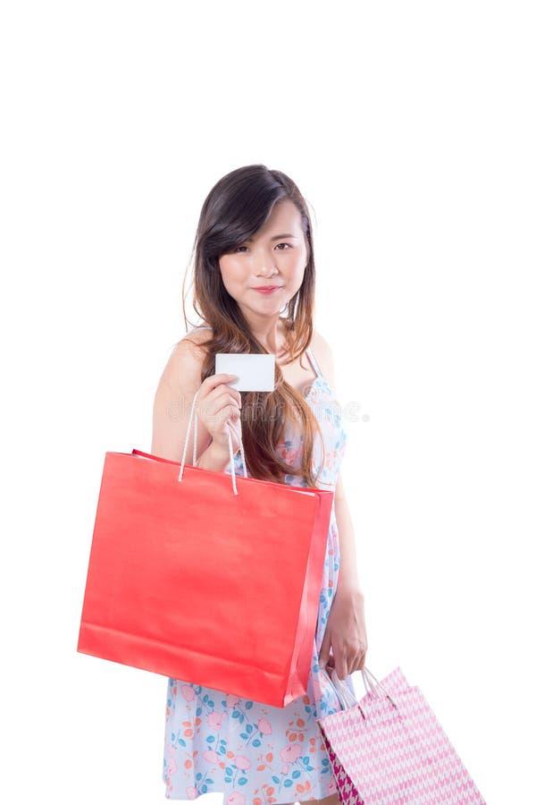 Giovane donna asiatica con il vestito rosso che tiene una carta di credito e un sacco di carta fotografia stock