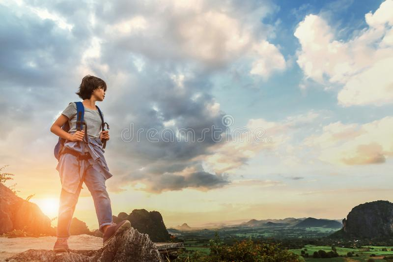 giovane donna asiatica con lo zaino che sta sullo sguardo superiore della montagna immagine stock libera da diritti