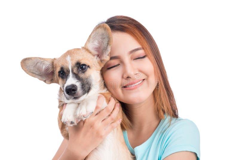 Giovane donna asiatica con un piccolo cucciolo isolato sopra una parte posteriore di bianco fotografia stock