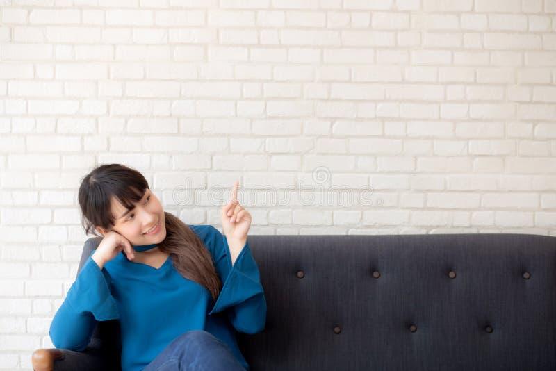 Giovane donna asiatica del bello ritratto che indica con lo spazio della copia sul fondo del calcestruzzo del cemento fotografia stock libera da diritti