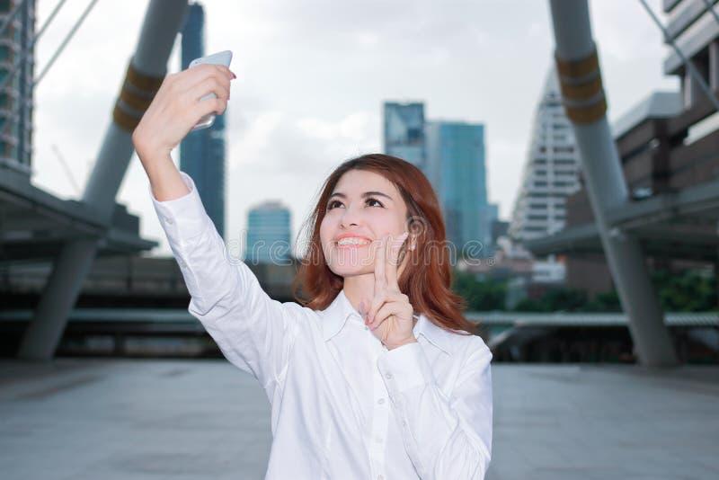 Giovane donna asiatica del fronte grazioso che prende una foto del selfie al fondo urbano della città Fuoco selettivo e profondit fotografie stock