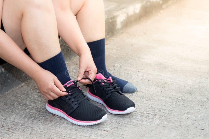 Giovane donna asiatica dell'atleta che lega le scarpe da corsa, corridore femminile pronto per pareggiare sulla strada fuori, ben fotografia stock libera da diritti