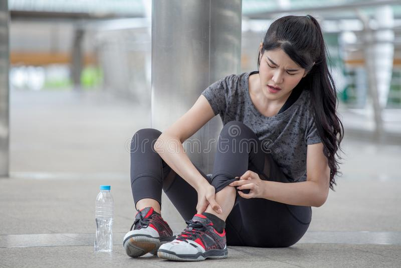 giovane donna asiatica di forma fisica che esegue incidente della gamba di lesione dell'allenamento che si esercita sulla via in  fotografia stock libera da diritti