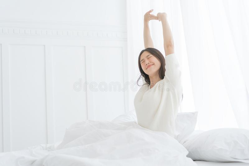 Giovane donna asiatica di mattina lei che allunga nel suo letto nella camera da letto fotografia stock libera da diritti