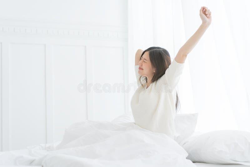 Giovane donna asiatica di mattina lei che allunga nel suo letto nella camera da letto fotografia stock