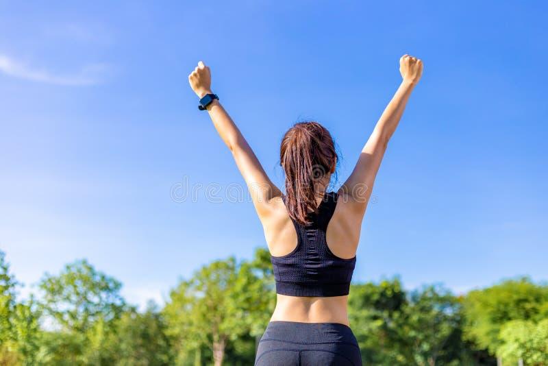 Giovane donna asiatica felice che alza sulle sue armi allegramente dopo completo la sua routine di esercizio ad un parco all'aper fotografia stock libera da diritti
