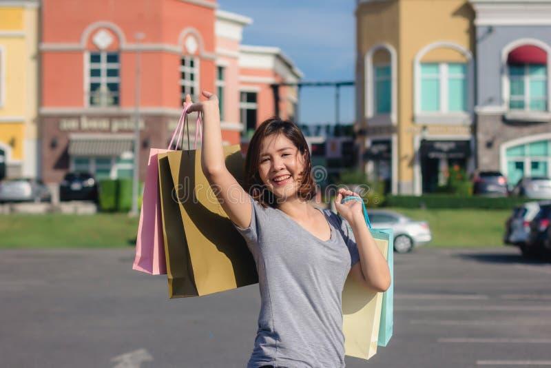 Giovane donna asiatica felice che compera un mercato all'aperto immagini stock