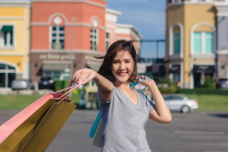 Giovane donna asiatica felice che compera un mercato all'aperto con fondo delle costruzioni e del cielo blu pastelli immagine stock libera da diritti