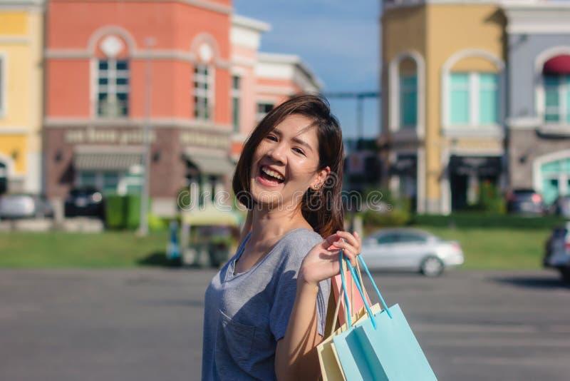 Giovane donna asiatica felice che compera un mercato all'aperto con fondo delle costruzioni e del cielo blu pastelli fotografia stock libera da diritti