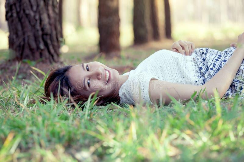 Giovane donna asiatica felice che si riposa sull'erba immagini stock