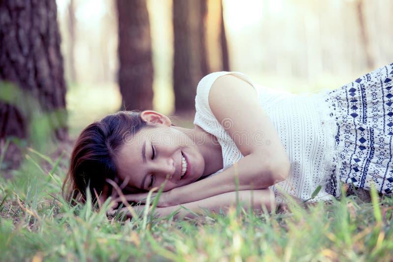 Giovane donna asiatica felice che si riposa sull'erba fotografie stock