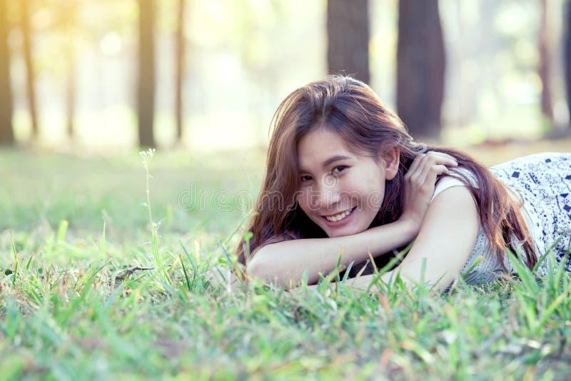 Giovane donna asiatica felice che si riposa sull'erba nel parco fotografia stock libera da diritti