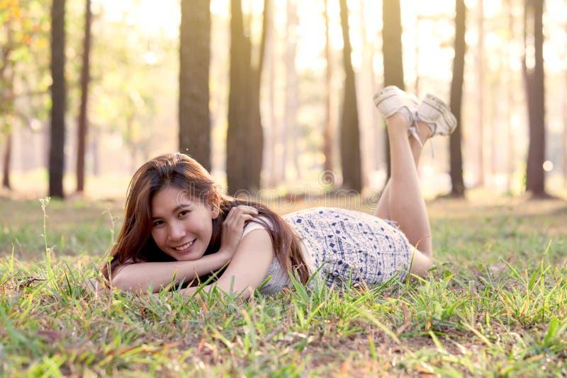 Giovane donna asiatica felice che si riposa sull'erba nel parco immagine stock libera da diritti