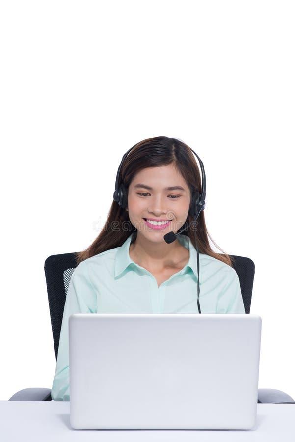 Giovane donna asiatica felice che si siede e che lavora con il computer portatile facendo uso della cuffia avricolare in ufficio immagini stock libere da diritti